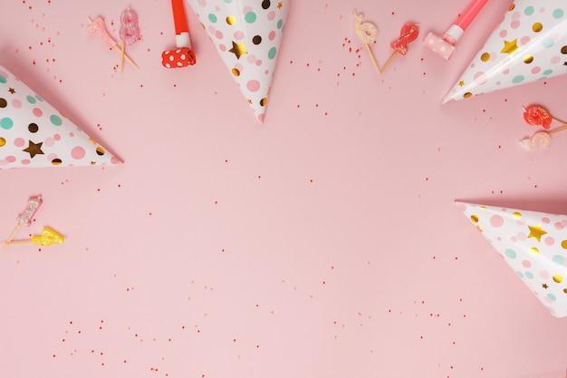 Feestmuts en kaarsen liggend op roze achtergrond