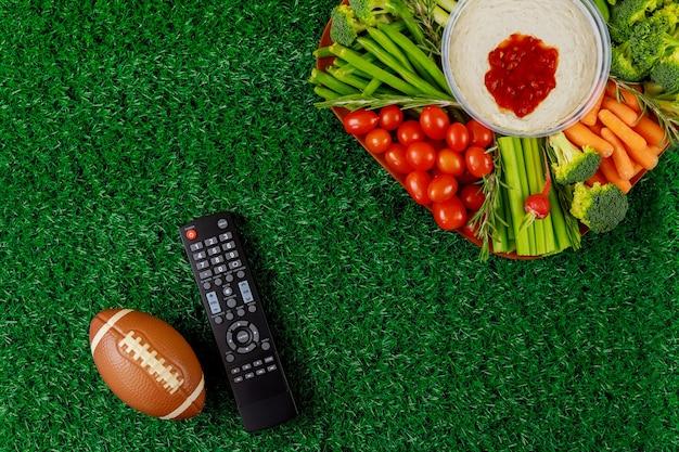 Feesttafel met afstandsbediening voor sport kijken naar american football-wedstrijd op tv.