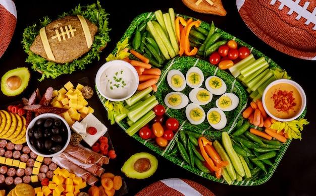 Feesttafel met eten en drinken voor het kijken naar american football-wedstrijd.