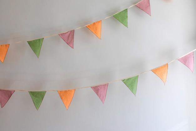 Feesttijd - kleurrijke slinger gemaakt van driehoekige textielvlaggen die op een witte muurachtergrond hangen