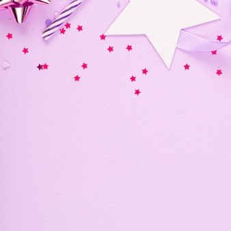 Feestvakantie-oppervlak met lint, sterren, verjaardagskaarsen en confetti op roze oppervlak