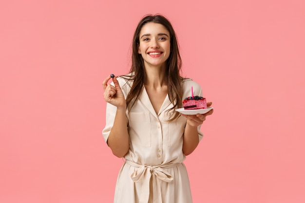 Feestvarken die heerlijke cake eten, kaars uitblazen en vreugdevol glimlachen, bosbes vasthouden, feestje vieren met vrienden, grijnzend in jurk over roze muur