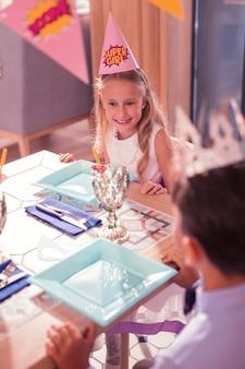Feestvarken glimlachend en wachten op het eten aan tafel