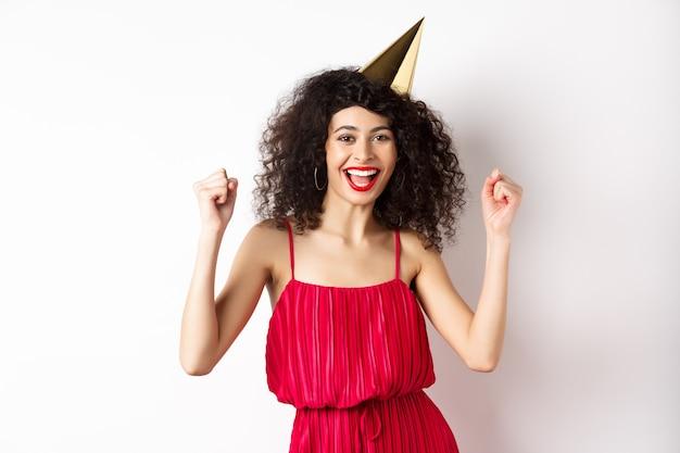 Feestvarken in feestmuts met plezier, dansen in een rode jurk en zingen, staande tegen een witte achtergrond.