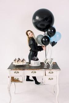 Feestvarken in zwarte jurk poseren met zwarte, witte, blauwe en grijze ballonnen. portret van gemiddelde lengte van aanbiddelijk jong meisje, dat zich dichtbij de lijst met cake, desserts en dranken op witte achtergrond bevindt