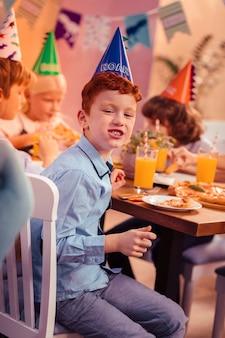 Feestvarken. vrolijke roodharige jongen die een glimlach op zijn gezicht houdt