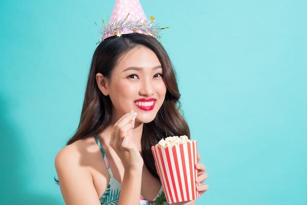 Feestvrouw poseren tegen blauwe muur in stijlvolle zomeroutfit, papieren hoed
