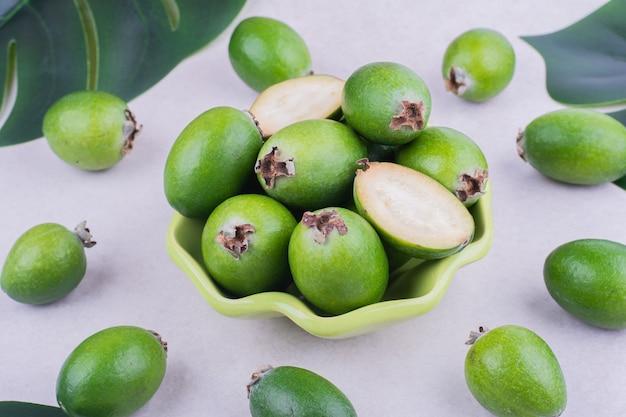 Feijoas in een groene kop op grijs oppervlak