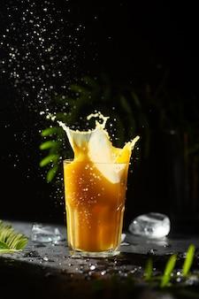 Fel oranje gekoeld drankje met citrus lude met spatten en druppels met groene plantenbladeren