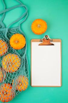 Fel oranje pompoenen in netje en lege kladblok voor boodschappenlijstje of recept