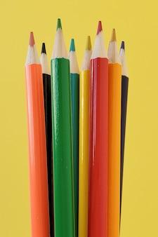 Fel veelkleurige potloden op een gele achtergrond creativiteit tekenen kindertijd