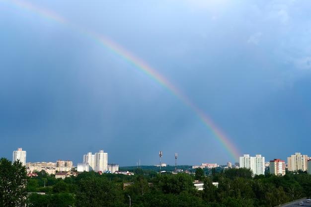 Fel veelkleurige regenboog boven de huizen van de stad in de blauwe lucht