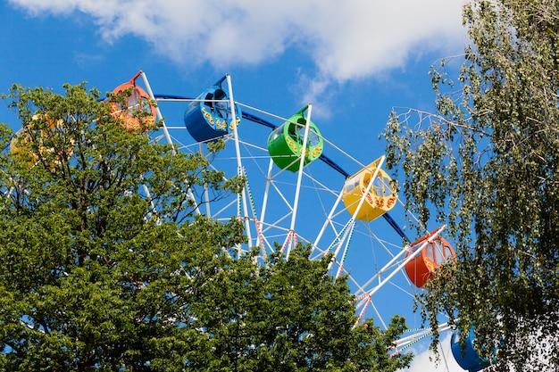 Felgekleurd reuzenrad in het park tegen een blauwe lucht met wolken.