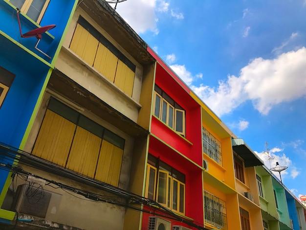 Felgekleurde commerciële gebouwen gedurende de dag met heldere blauwe luchten.