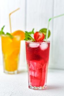 Felgekleurde heerlijke koude limonade van aardbei en sinaasappel met munt op lichte ondergrond