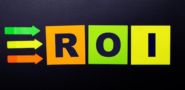 Felgekleurde papieren stickers op een zwarte tafel met de tekst roi