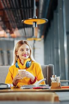 Felgele trui blondharige vrouw met felgele trui die koffie drinkt in restaurant