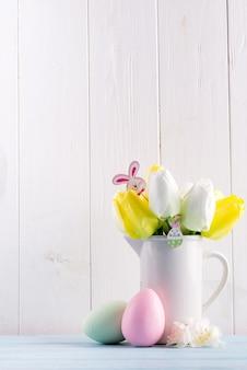 Felicitatie paaskaart met verse tulpen, handgemaakte beschilderde eieren en decoratie tegen lichtgrijze houten muur