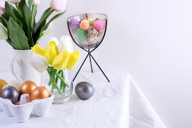 Felicitatie paaskaart van gediende tafel met lentebloemen en handgemaakte beschilderde eieren tegen lichtgrijze muur.