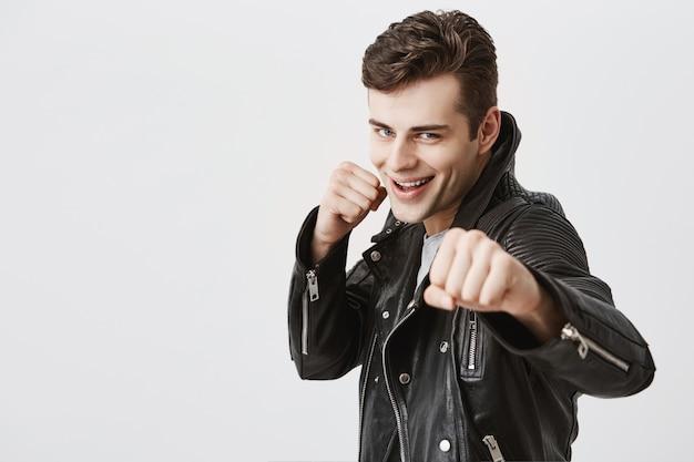 Felle en zelfverzekerde jonge knappe man in zwarte leren jas die vuisten voor zich houdt alsof hij klaar is om te vechten of voor een uitdaging, glimlachend met tanden, met vastberaden uitdrukking op zijn gezicht