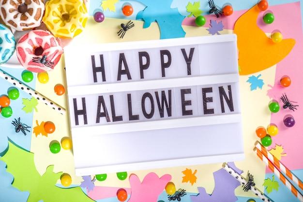 Felle kleur mockup feestuitnodiging, menu, wenskaart voor halloween-vakantie. trendy kleurrijke achtergrond met papieren halloween-symbolen spook, vleermuizen, snoepjes, cocktailbuizen. bovenaanzicht frame kopie ruimte