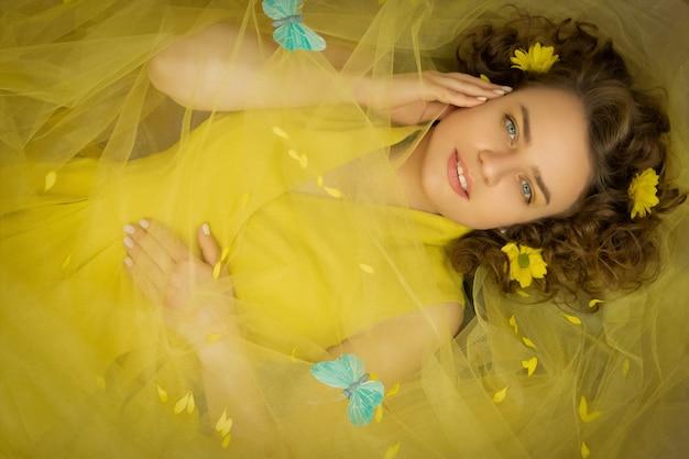 Felle zonneschijn vrouw in gele jurk met gele bloemen close-up.art processing