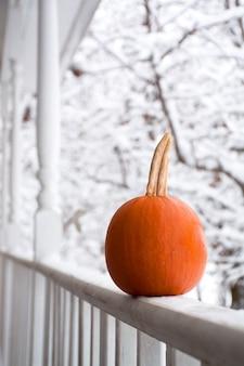 Feloranje pompoen op veranda herfstversieringen op veranda hallo winter eerste sneeuw