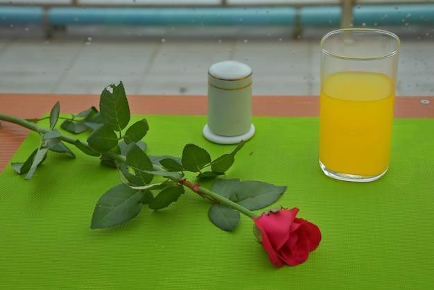 Felrode roos mooi geplaatst naast een glas sinaasappelsap