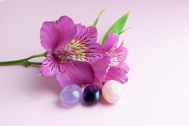 Felroze bloemen van alstroemeria op een roze ondergrond en de mineralen van amethist en rozenkwarts