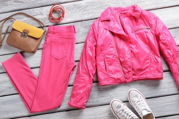 Felroze jas en broek bruine tas en witte schoenen meisjes leren armbanden op showcase extreem...
