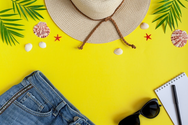 Female straw hat, shorts, sunglasses, notepad for entries