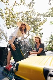 Femannelijke reizigers die koffers in de kofferbak stoppen