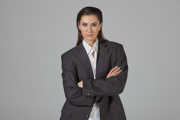 Feminisme en mannelijkheid concept. mooie modieuze jonge donkerharige vrouw mannen jas dragen over wit overhemd kruising armen op haar borst, zelfverzekerd kijken