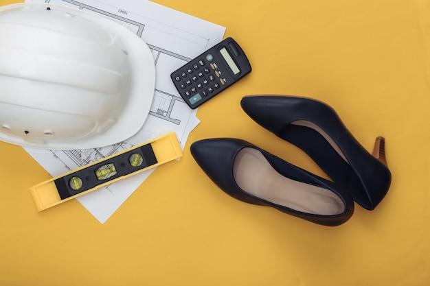 Feminisme, mannenwerk wordt gedaan door vrouwen. hoge hakken voor dames, technische benodigdheden op een geel.