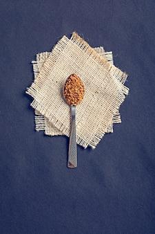 Fenegriekzaden in een lepel op zwarte houten raad