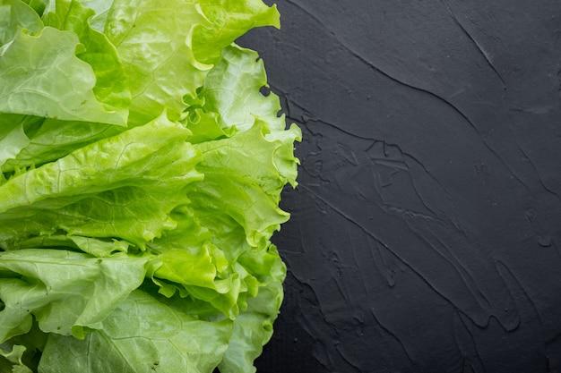 Fesh groene sla salade biologische bladeren, op zwarte tafel