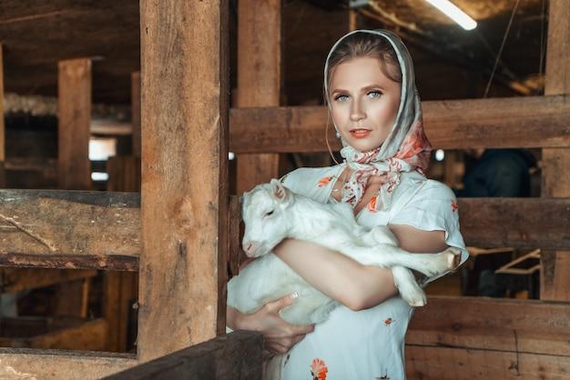 Feshion vrouw op de boerderij met een kleine geit in haar armen