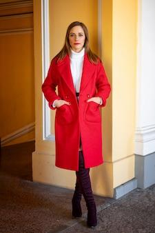 Feshionvrouw in een rood jasje dat zich op de straat bevindt