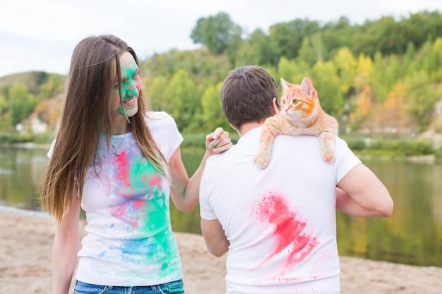 Festival holi, vakantie, toerisme, huisdier en natuur concept - portret van vrouw en man met kat bedekt veelkleurig stof