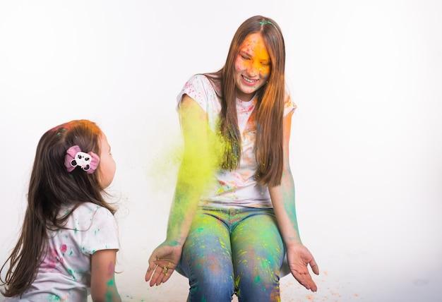 Festival van holi, mensen en vakantie concept - meisje speelt met haar moeder bedekt met verf