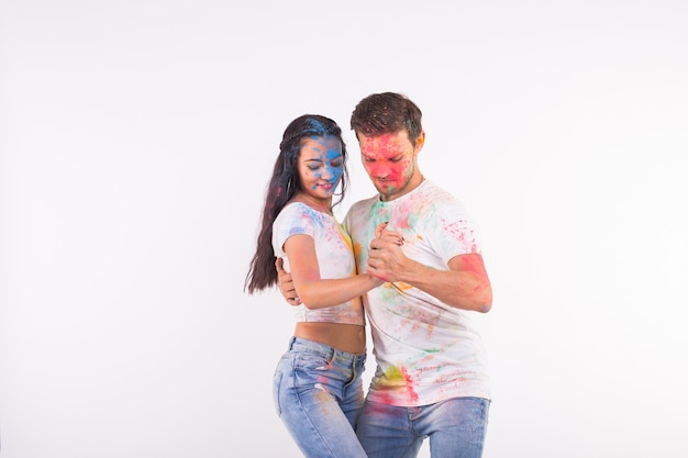 Festival van holi, sociale dans, vriendschap - jongeren spelen met kleuren op het festival van holi en dansende bachata of kizomba op wit oppervlak met kopie ruimte