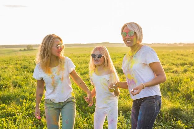 Festival van holi, vriendschap, geluk en vakantieconcept - kleine meisjes en vrouwen in glazen die op het festival van holi knuffelen.