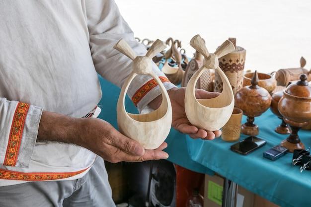 Festival van volksambachten een man houdt handgemaakte houtproducten in zijn handen