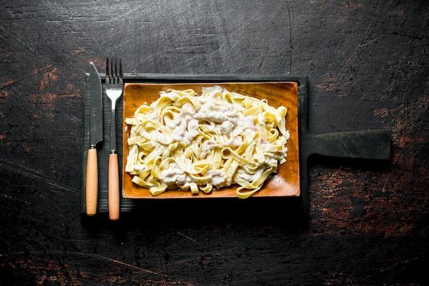 Fettuccine met carbonara-saus op een bord met mes en vork. op rustieke tafel