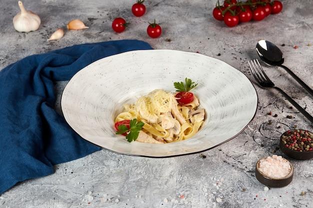 Fettuccine met kip en champignons, grijze achtergrond