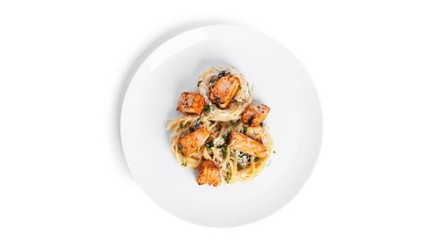 Fettuccine met zalm en rucola in geïsoleerde roomsaus. pasta nesten geïsoleerd.