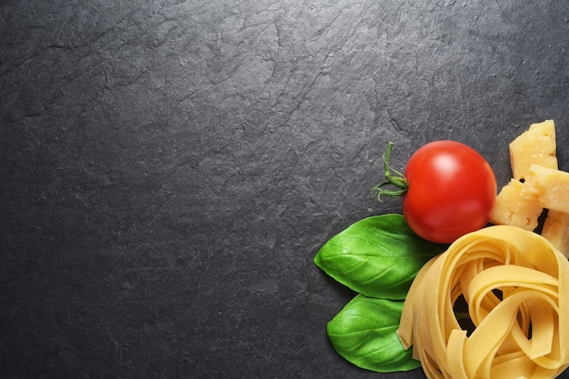 Fettuccine pasta met basilicum bladeren, parmezaanse kaas en tomaat op zwarte leisteen achtergrond met kopie ruimte