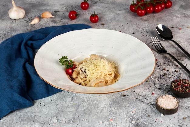 Fettuccine pasta met eekhoorntjesbrood in een romige saus, grijze achtergrond