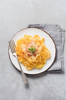 Fettuccine pasta met parmezaanse kaas in lichte plaat op oude witte betonnen ondergrond. bovenaanzicht.