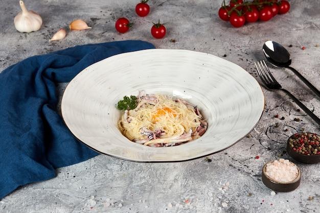Fettuccine pasta met rundvlees en ei in een romige saus, grijze achtergrond